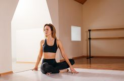 Woman stretching seated spinal twist. Young slim girl makes exercise. Fit woman stretching back exercise for spine warm up concept at home Stock Photos