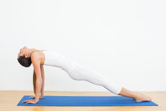 Fit woman stretching body in the fitness studio Stock Photos