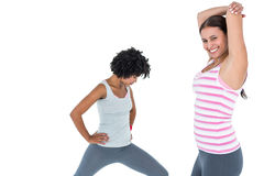 Fit woman stretching while female friend exercising Stock Photo
