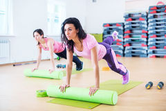 Fit woman stretching on floor using foam roller doing plank exercise. Fit women stretching on floor using foam roller doing plank exercise Stock Photo