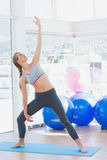 Fit woman stretching hand in fitness studio Stock Images