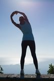 Fit woman stretching her arms looking out to sea Stock Photos