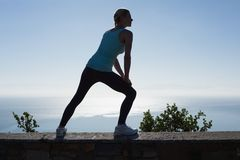 Fit woman stretching her legs looking out to sea Stock Photos