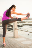 Fit woman stretching leg on railing Royalty Free Stock Photography