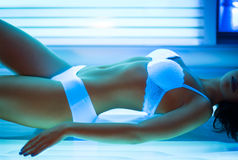 Fit woman sunbathing in solarium. Young fit woman sunbathing in solarium Royalty Free Stock Photos