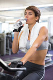 Fit woman taking a drink on the exercise bike Stock Photos