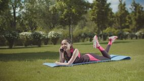 Fit woman talking on phone lying on mat outdoors stock footage