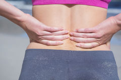 Fit woman touching her sore back. On a sunny day Royalty Free Stock Photography