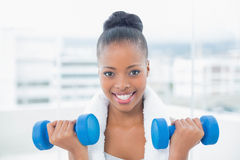 Fit woman with towel around her neck working out with dumbbell Stock Image