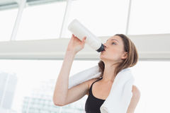 Fit woman with towel around neck drinking water in fitness studio Royalty Free Stock Image