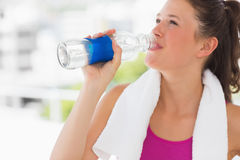 Fit woman with towel drinking water in gym Stock Image