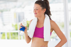 Fit woman with towel drinking water in gym Royalty Free Stock Photography