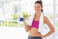 Fit woman with towel and water bottle in gym Royalty Free Stock Images