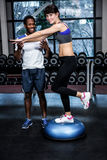 Fit woman with trainer exercising with bosu Stock Image