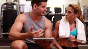 Fit woman and trainer talking about her progress Stock Photography