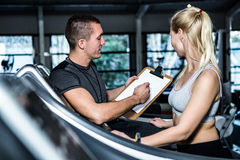 Fit woman with trainer using treadmill Stock Images