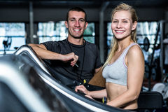 Fit woman with trainer using treadmill Royalty Free Stock Photo
