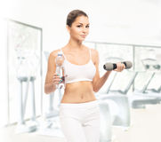 A fit woman training with dumbbells in a gym Stock Images
