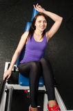 Fit woman training on fitness simulator at gym Stock Photos