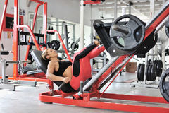 Fit woman training legs on a leg simulator at the gym Stock Images