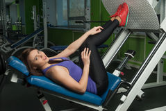 Fit woman training legs on leg simulator at gym Royalty Free Stock Images