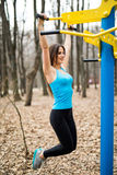Fit woman training pull ups in city park outdoors. Health concept. Royalty Free Stock Photography