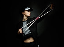 Fit woman training with resistance band against black background Royalty Free Stock Images