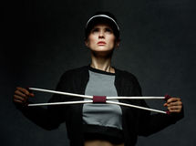 Fit woman training with resistance band against dark background Royalty Free Stock Photography