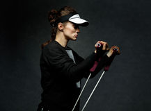 Fit woman training with resistance band against dark background Stock Photo