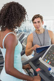 Fit woman on treadmill talking to personal trainer Royalty Free Stock Photography