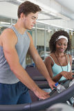 Fit woman on treadmill talking to personal trainer Stock Photo