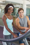 Fit woman on treadmill talking to personal trainer Royalty Free Stock Images