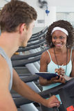 Fit woman on treadmill talking to personal trainer Royalty Free Stock Photo