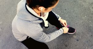 Fit woman tying her shoe lace 4k. High angle view of fit woman tying her shoe lace 4k stock video footage
