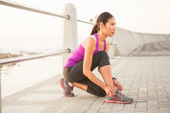 Fit woman tying shoelace at promenade Stock Photography