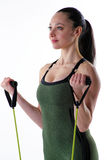 Fit woman using exercise bands. Image of a fitness model doing a biceps curl with an exercise band Royalty Free Stock Photo