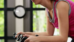 Fit woman using exercise bike stock footage