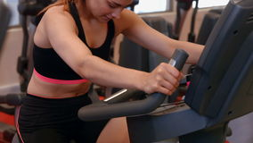 Fit woman using exercise bike in gym stock video