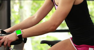Fit woman using exercise bike and smart watch stock video