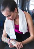 Fit woman using fitness band in gym against spiral dots in background. Digital composition of fit woman using fitness band in gym against spiral dots in stock photo