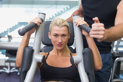 Fit woman using fitness machine at gym Royalty Free Stock Photos