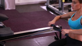 Fit woman using the rowing machine stock footage