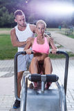 Fit woman using rowing machine Stock Photos