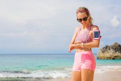 Woman using wearable tech while exercising outdoors stock image