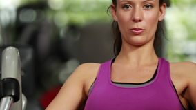 Fit woman using weight machine stock video
