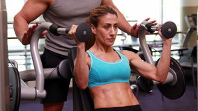 Fit woman using weights machine for arms with her trainer Royalty Free Stock Images