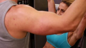 Fit woman using weights machine for arms with her trainer Royalty Free Stock Photography
