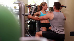 Fit woman using weights machine for arms with her trainer Stock Image