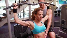 Fit woman using the weights machine for her arms while trainer supervises Stock Images