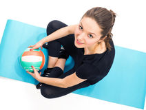 Fit woman with volley ball sitting on exercise mat. Fit woman with volley ball sitting on exercise  blue mat Royalty Free Stock Photography